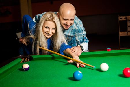 billiards halls: Beautiful cheerful couple plays billiard.