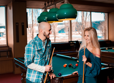 snooker hall: Beautiful couple having fun and playing billiards.