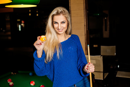 cue: beautiful young blonde with cue ball in hand smiling.