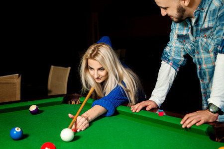 billiards hall: Beauty young blonde woman plays billiard for the first time with a teacher.