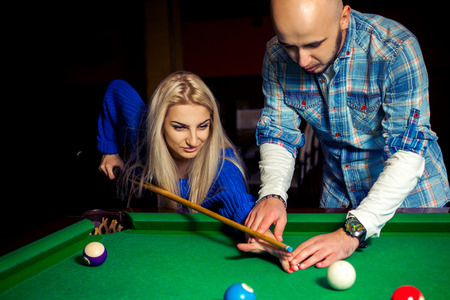 snooker hall: Man teaches girl how to hit in billiards.