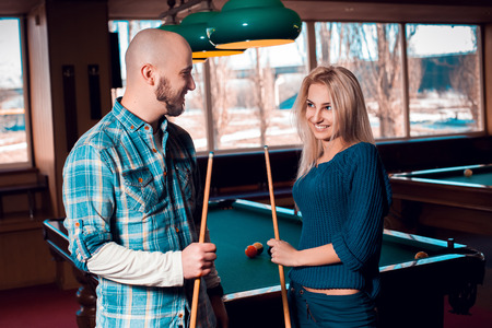 billiards halls: Charming young couple smiling at each others and plays billiard.