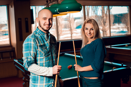 snooker halls: Cute young couple plays billiard and having some fun.