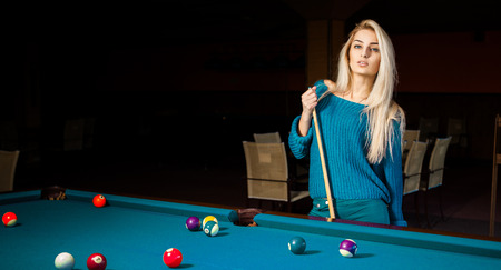 sexual activities: Fashion portrait of beautiful young blonde girl plays billiard. Stock Photo