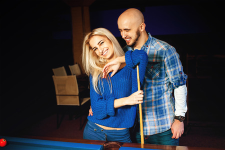fashionable couple: Fashionable couple having fun and plays billiard. Stock Photo