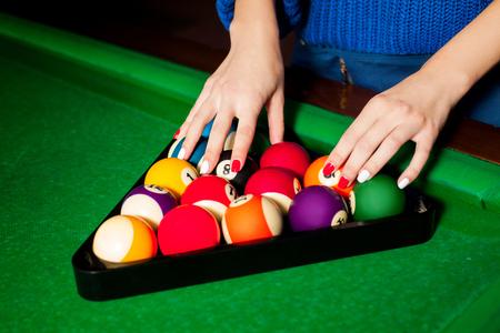 billiards cue: female hands are arranged billiard balls in triangle. Stock Photo