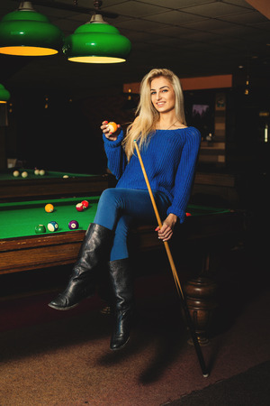 adult sexual: Fun sexual lady posing on pool table with the cue and ball in hands. Stock Photo