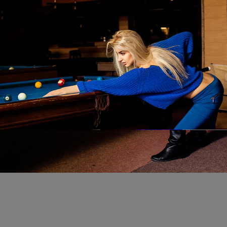 human sexual activity: Portrait of sexual blonde woman with cue plays billiard. Stock Photo