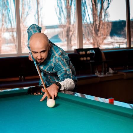 cue: Man preparing to hit the cue ball on a pool billiards. Stock Photo