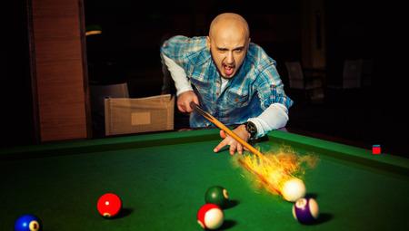 sexual activities: angry man hits fireball at pool billiard. Stock Photo