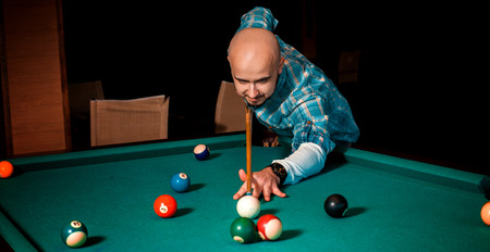 sexual activities: Horizontal portrait of concentrated man plays on billiard table.