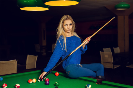 pool cue: Horizontal portrait of serious blonde woman posing with the cue in hands at pool table.