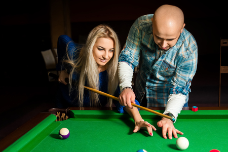 snooker hall: Teacher shows a girl how to play pool billiard.