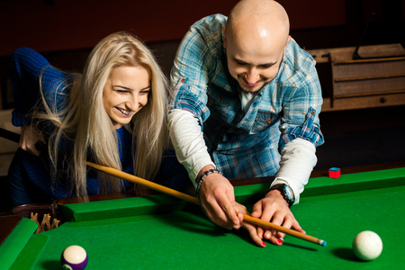 billiards hall: Man teaches his girlfriend how to play on the pool table.