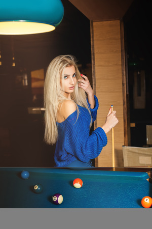 pool cue: Sensual young blonde lady posing on pool table with the cue. Stock Photo