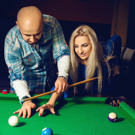 snooker hall: Square portrait of beautiful couple plays billiard on the pool table.