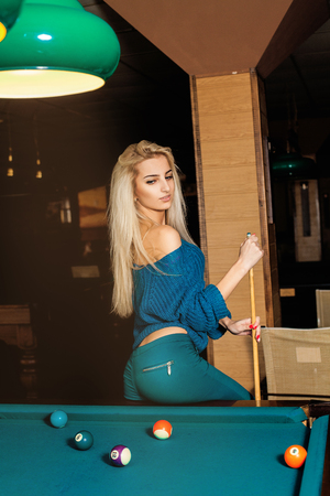 pool cue: Vertical portrait of young fashionable girl posing on pool table with the cue.