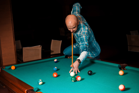 sexual: man chooses a difficult hit on pool billiards.