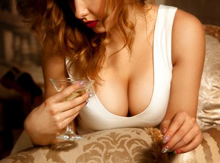 hot breast: Закрыть фото сексуальной большой женской груди и стакан мартини.