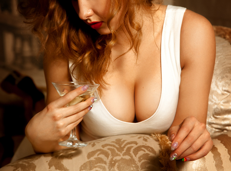 Close up photo of sexual big female breast and glass of martini.