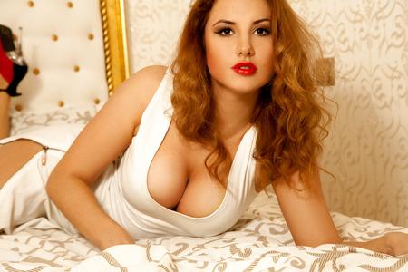 big boobs: dama Morena rizada con grandes tetas naturales que miran a la cámara.