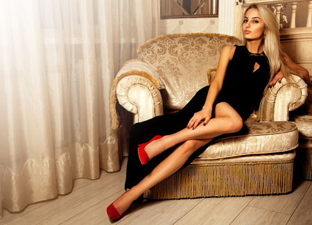 Adorable hot blonde woman in long black dress and red high heels.
