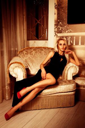 lusso attraente sottile donna bionda in abito lungo nero e tacchi rossi, guardando la fotocamera.