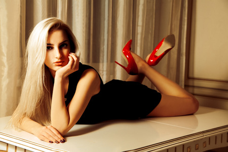 Beautiful blonde woman with seduction look lying on table.