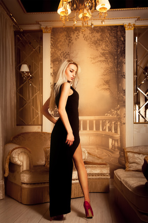 High society blonde sexy woman in long black dress and high heels looking away.