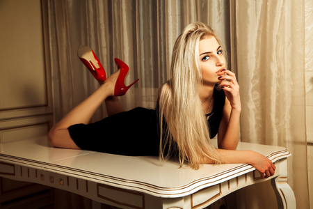 seduction: Lovely blonde woman lying on table with seduction look. Stock Photo