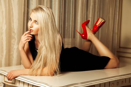 seduction: Pretty blonde with seduction look lying on table. Stock Photo