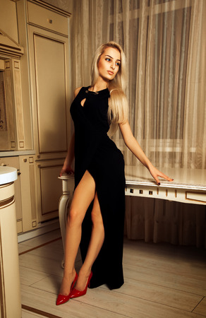 Vertical photo of sexual beauty woman in long black dress and red high heels.