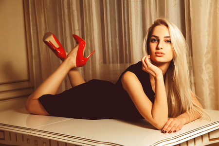 seduction: Young beautiful blonde woman lying on table with seduction look. Stock Photo