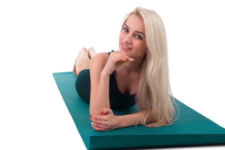 niñas sonriendo: Young girl practicing yoga with gymnastic mat
