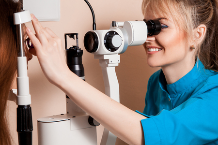 fundus: Attractive happy female ophthalmologist is working in clinic. Stock Photo