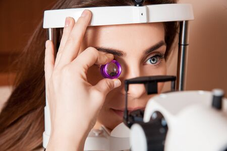 fundus: Beautiful adult woman patient during an eye examination at the eye clinic.