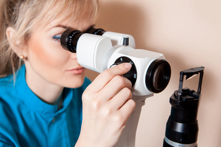 fundus: Serious young adult Doctor optometrist at work with the device for testing vision.