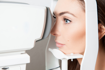 visual therapy: Sweet young adult brunette looking at eye test machine in ophthalmologist. Stock Photo