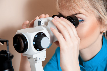 testing vision: young charming Doctor optometrist at work with the device for testing vision.