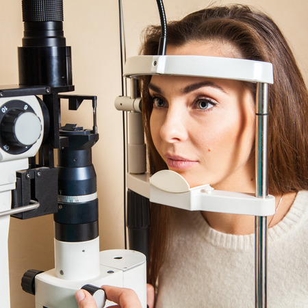 performed: Young woman is having eye exam performed by eye doctor.