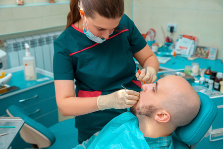 odontolith: Attractive brunette woman dentist treat teeth of her patient. Stock Photo