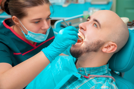 odontolith: guy checks his teeth in dental office. Stock Photo
