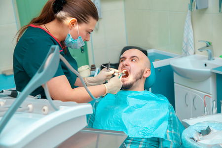 odontolith: Angry patient with dentist in dental office checks teeth.