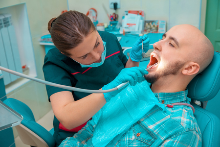 odontolith: charming girl dentist checks the teeth of her patient. Stock Photo