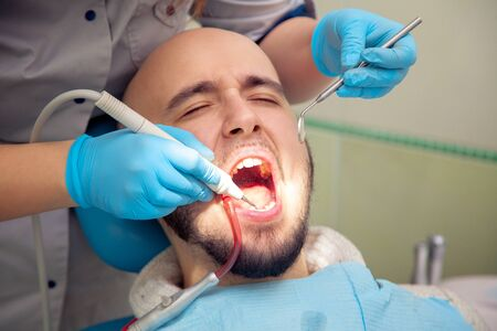 odontolith: close up photo of handsome guy treats caries teeth in the dental office Stock Photo
