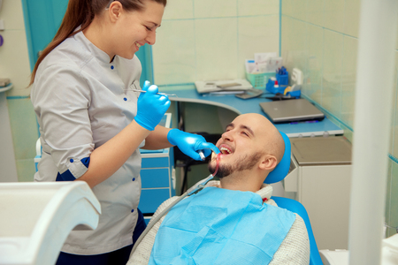 odontolith: Woman dentist checks the teeth of her patient in the dental office. Stock Photo
