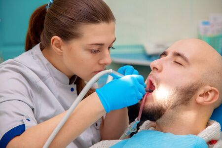 odontolith: Dentist curing a male patient.