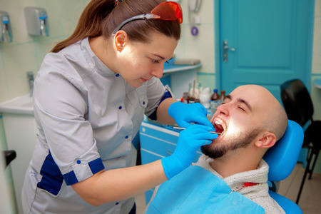 odontolith: Female dentist treats teeth patient.