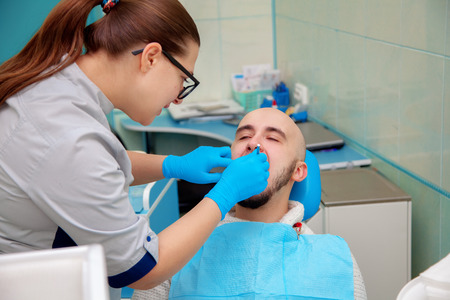 odontolith: guy in the dental office checks the teeth. Stock Photo
