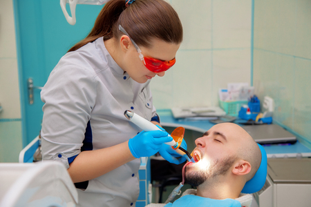 odontolith: guy treats his teeth in a dental office at the doctor.